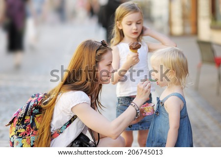 Young mother and her daughters eating ice cream outdoors  - stock photo
