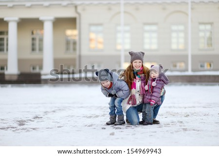 Young mother and her daughters having fun on winter day - stock photo