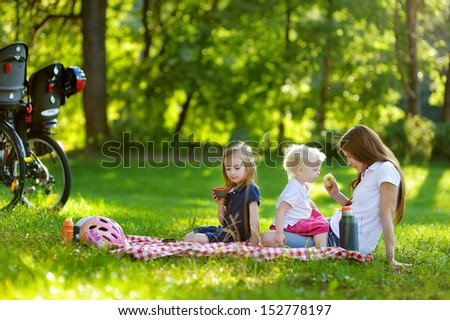 Young mother and her daughters picnicking in the park - stock photo