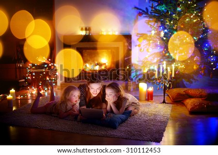 Young mother and her daughters using a tablet pc by a fireplace on warm Christmas evening - stock photo