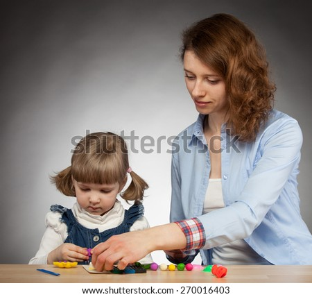 Young mother and her daugther modelling with plasticine; dark background - stock photo