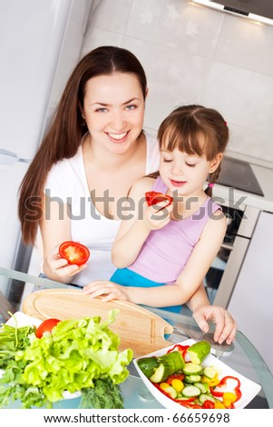 young mother and her five year old daughter cook together on the kitchen at home (focus on the woman) - stock photo