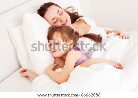 young mother and her five year old daughter sleep on the bed at home (focus on the child) - stock photo