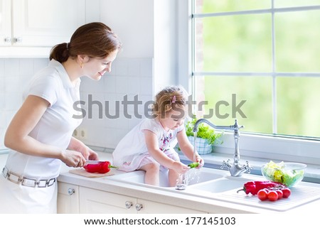 Young mother and her funny curly toddler daughter washing vegetables together in a kitchen sink getting ready to make salad for lunch in a sunny white kitchen with a big garden view window - stock photo