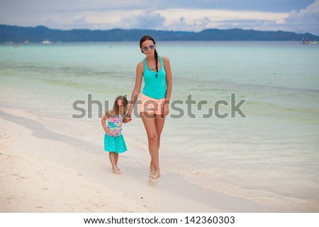 Young mother and her little daughter enjoying beach vacation - stock photo