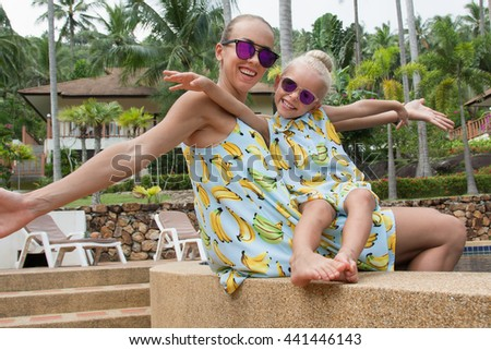 Young mother and her little daughter have fun near the swimming pool. - stock photo
