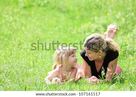 young mother and her little daughter on the nature - stock photo