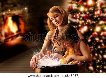 Young mother and her little daughter reading book sitting at the Christmas tree, fireplace - stock photo
