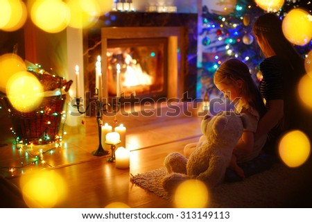 Young mother and her little daughter sitting by a fireplace in a cozy dark living room on Christmas eve - stock photo