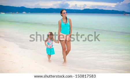 Young mother and her little daughter walking by the sea on Philippines - stock photo