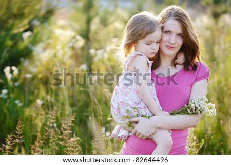 Young mother and her little girl in a meadow - stock photo