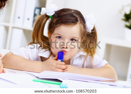 Young mother and her little girl studying together at home - stock photo