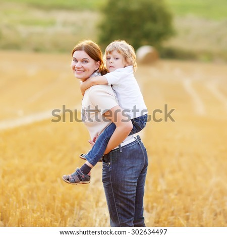 Young mother and her little son having fun on yellow hay field in summer. Happy family of two enjoying nature and togetherness. Boy riding on mum. - stock photo