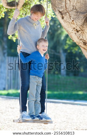 young mother and her little son having fun together at swings in the park - stock photo
