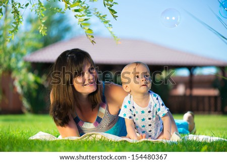 Young mother and her little son looking at soap bubbles - stock photo