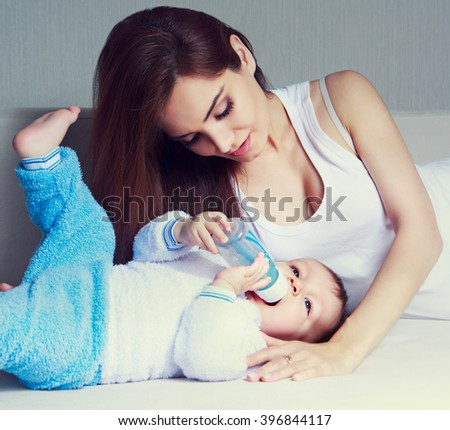 young mother and her one year old baby at home - stock photo