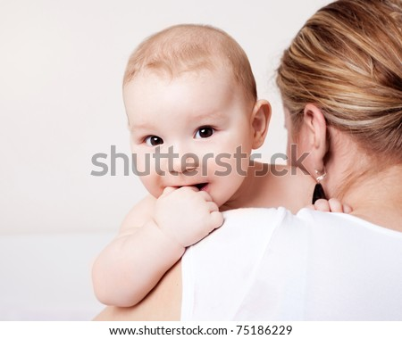 young  mother and her six months old baby at home - stock photo