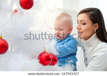 young mother and her son decorate white Christmas tree - stock photo
