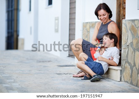 Young mother and her son having rest outdoors in city on beautiful summer day - stock photo