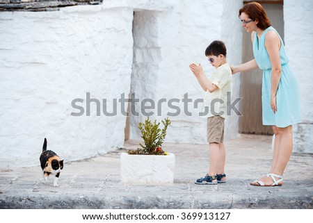 Young mother and her son met a cat while walking narrow streets ot typical italian town - stock photo
