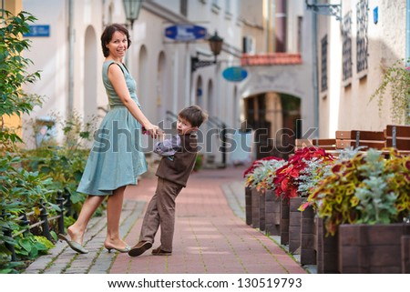 Young mother and her son walking outdoors in city - stock photo