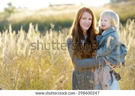 Young mother and her toddler girl at autumn - stock photo