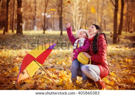 Young mother and her toddler girl have fun in autumn - stock photo