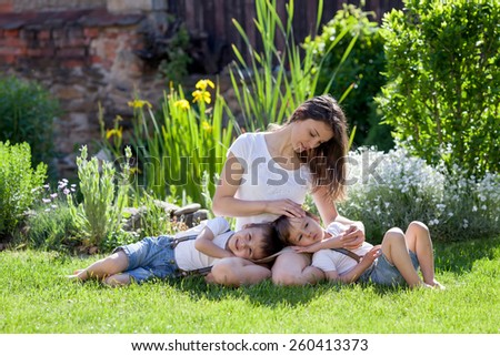 Young mother and her two children, boys, sitting on a lawn, tenderness. Mother cuddling them - stock photo