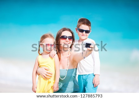 Young mother and her two kids taking self portrait with compact camera - stock photo