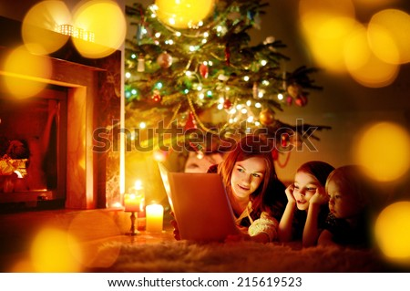 Young mother and her two little daughters reading a book by a Christmas tree in cozy living room in winter - stock photo
