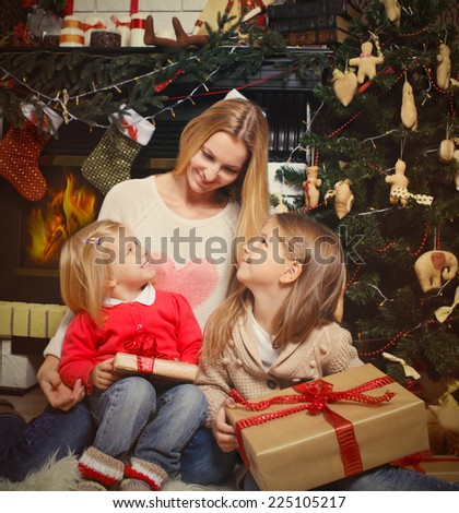 Young mother and her two little daughters with Christmas gifts by a Christmas tree in cozy living room with fireplace in winter - stock photo