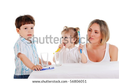 young mother and her young daughter and son brushing teeth on a white background - stock photo