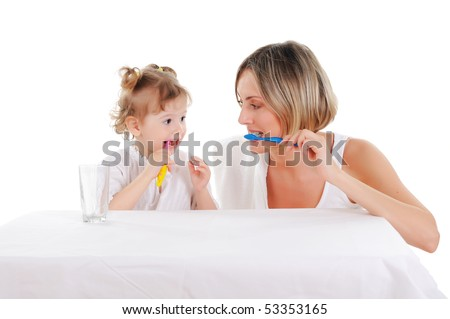 young mother and her young daughter brush their teeth on a white background - stock photo