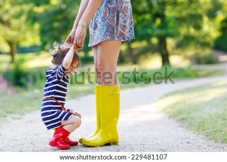 Young mother and little adorable child girl in rubber boots having fun together, family look, in summer park on sunny warm day. Long legs of woman. - stock photo