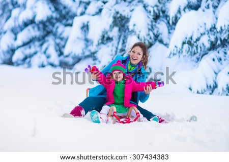 Young mother and little girl enjoying sleigh ride. Child sledding. Toddler kid riding sledge. Children play outdoors in snow. Kids sled in snowy park. Outdoor winter fun for family Christmas vacation. - stock photo