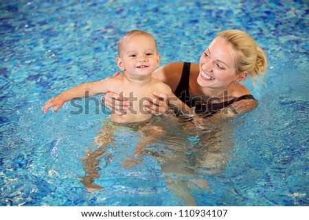 Young mother and little son having fun in a swimming pool - stock photo