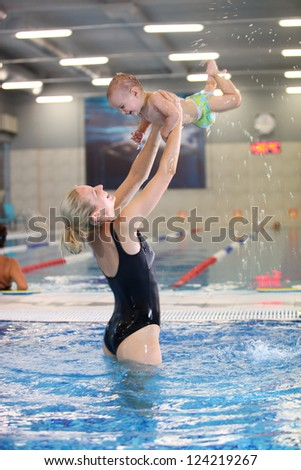 Young mother and little son having fun in a swimming pool, motion blurred image - stock photo