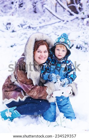 Young mother and little toddler boy having fun with snow outdoors on beautiful winter day - stock photo