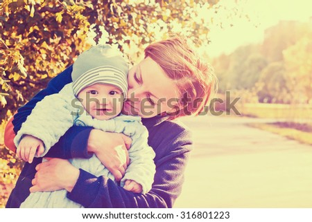 Young mother and newborn baby cute outdoor portrait. Vintage style toned image - stock photo
