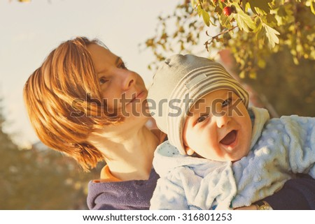 Young mother and newborn baby fun outdoor portrait. Vintage image - stock photo