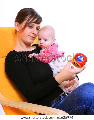 Young mother and newborn daughter with plastic toy. - stock photo