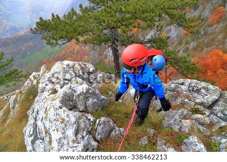 Young mother and small child climb a steep ridge on the mountain  - stock photo