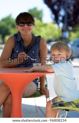 Young mother and son eating ice cream in a street cafe on a warm summer day - stock photo