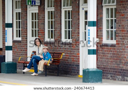 Young mother and son waiting for train on railway station platform - stock photo