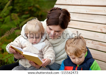 Young mother and toddler reading book in autumn park - stock photo