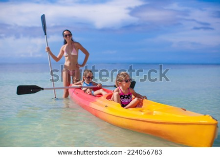 Young mother and two her little daughters kayaking at tropical warm sea - stock photo