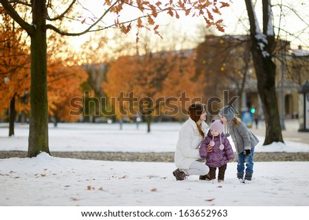 Young mother and two kids having fun on winter day - stock photo
