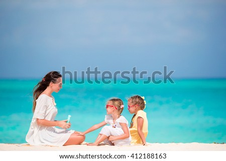 Young mother applying sunscreen on her kids at the beach - stock photo