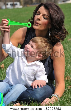 young mother blowing bubbles with her toddler son outside - stock photo