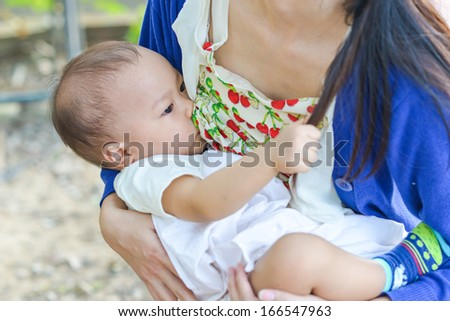Young mother breast feeding her infant.  - stock photo